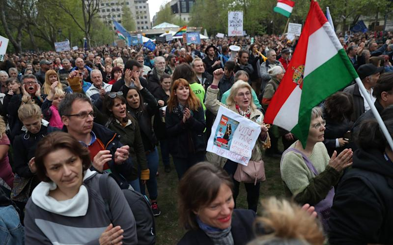 Demonstrators protest against Hungarian Prime Minister Viktor Orban's government in front of the former building of Hungarian Television on April 15, 2017 - Credit: FERENC ISZA/AFP