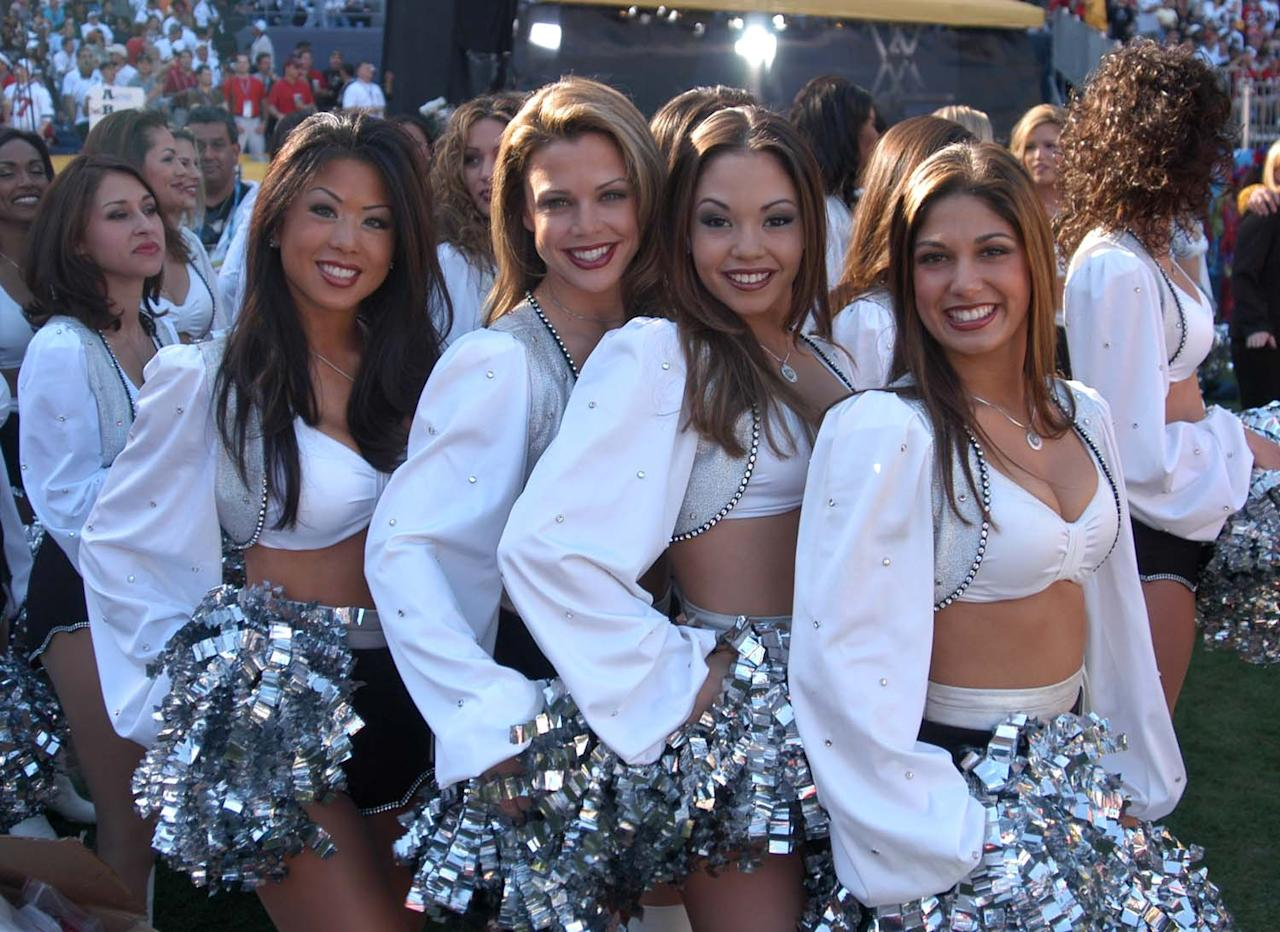 Cheerleaders from the Oakland Raiders stand on the sidelines during Super Bowl XXXVII versus Tampa Bay.  (Photo by Jason Nevader/Getty Images) *** Local Caption ***