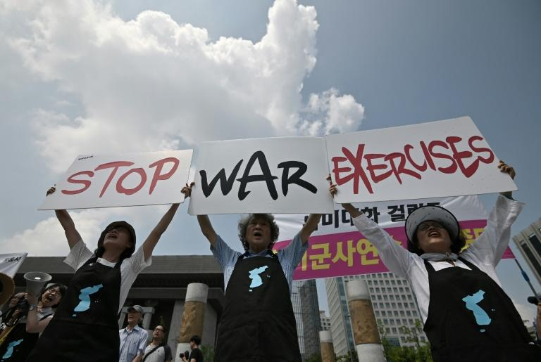 Anti-war activists hold placards during a rally against planned South Korea-US annual joint military exercises near the US embassy in Seoul