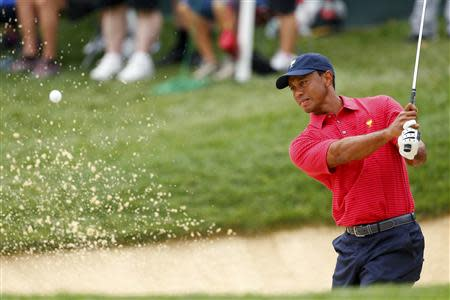U.S. Team player Tiger Woods hits out of a bunker on the 12th hole during the second practice round for the 2013 Presidents Cup golf tournament at Muirfield Village Golf Club in Dublin, Ohio