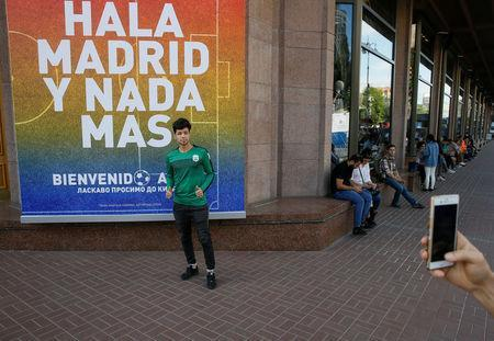 A man poses for a picture next to a banner with the FC Real Madrid's slogan in central Kiev, Ukraine May 22, 2018. REUTERS/Valentyn Ogirenko