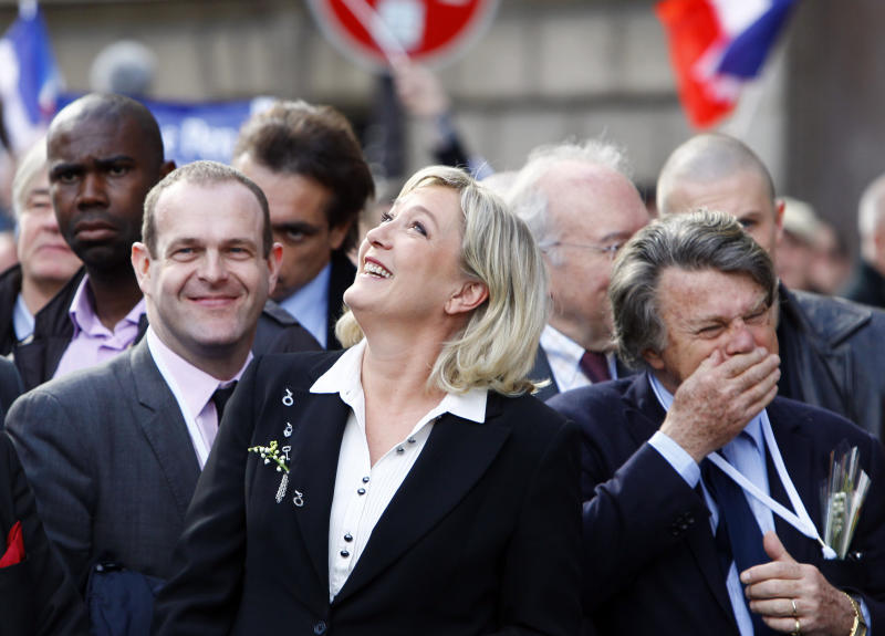 France's far-right National Front candidate for the presidential election Marine Le Pen, center, with lawyer Gilbert Collard, right, walk toward the statue of Joan of Arc, during the traditional May Day march in Paris, Tuesday May 1, 2012.  After Socialist party candidate Francois Hollande won a slim upper hand in the first round of voting, President and conservative candidate Nicolas Sarkozy candidly ogled voters of the far-right National Front whose candidate, Marine Le Pen, placed a solid third. (AP Photo/Francois Mori)