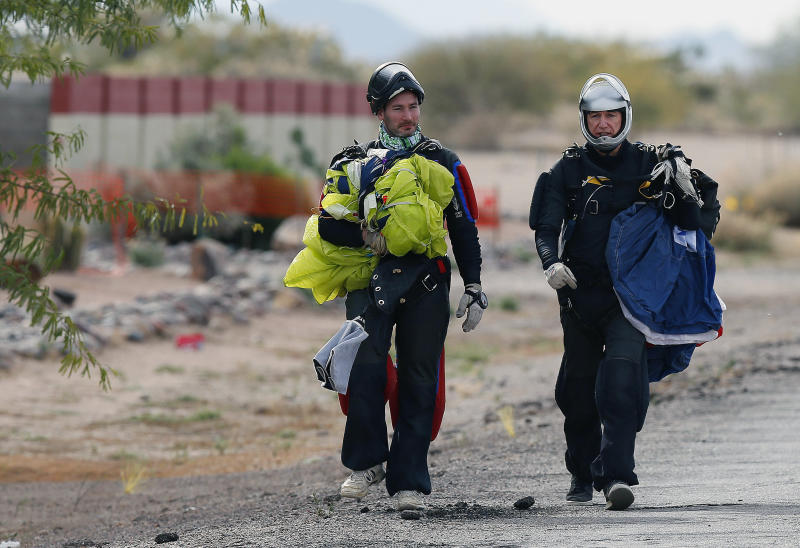 Two skydivers, who did not want to speak to the media, walk back to the airport after they joined nearly 200 skydivers, from all over the world, to perform a group jump the day after two skydivers were killed after colliding in midair during a jump from Skydive Arizona at Eloy Municipal Airport, on Wednesday, Dec. 4, 2013, in Eloy, Ariz. (AP Photo/Ross D. Franklin)