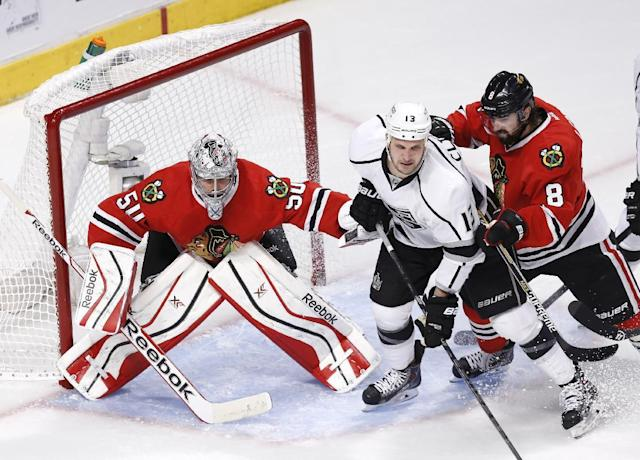 In this photo taken Sunday, May 18, 2014, Chicago Blackhawks defenseman Nick Leddy (8) checks Los Angeles Kings left wing Kyle Clifford (13) away from the goal and goalie Corey Crawford (50) during the second period of Game 1 of the Western Conference finals in the NHL hockey Stanley Cup playoffs in Chicago. The Blackhawks' defense is playing a key role in this postseason run as the Kings found out how hard it is to score on the defending Stanley Cup champions. (AP Photo/Charles Rex Arbogast)