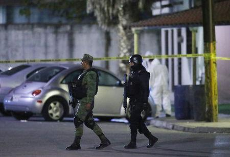 A soldier and a police officer stand guard as a forensic technician works at a crime scene, where men were killed inside a home by unknown assailants, in the municipality of San Nicolas de los Garza, Mexico, January 27, 2018. Picture taken January 27, 2018. REUTERS/Jorge Lopez