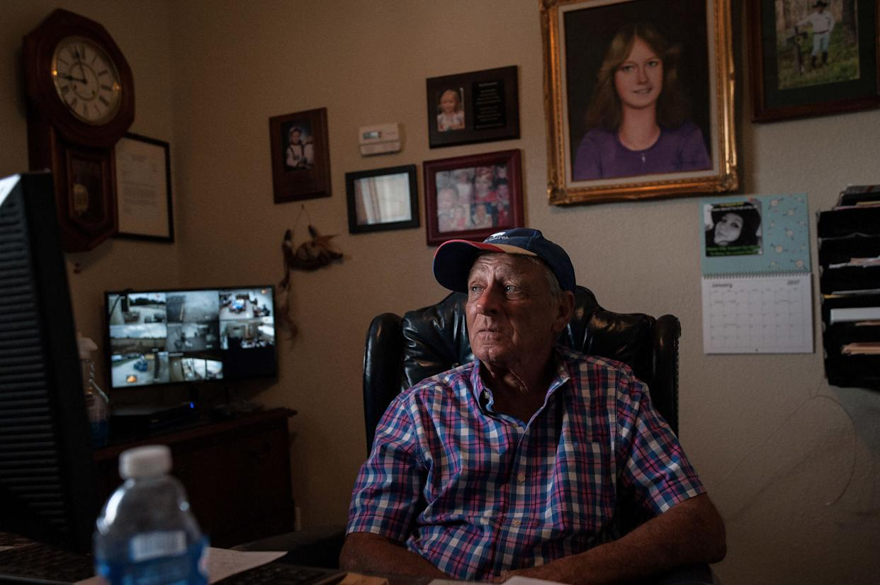 """Tim Miller, founder and director of EquuSearch, sits in his office in front of a portrait of his daughter, Laura, who was abducted and murdered in 1984. Miller founded EquuSearch in 2000 in honor of her. (Photo: <a href=""""https://josephrushmore.com/"""" rel=""""nofollow noopener"""" target=""""_blank"""" data-ylk=""""slk:Joseph Rushmore for HuffPost"""" class=""""link rapid-noclick-resp"""">Joseph Rushmore for HuffPost</a>)"""
