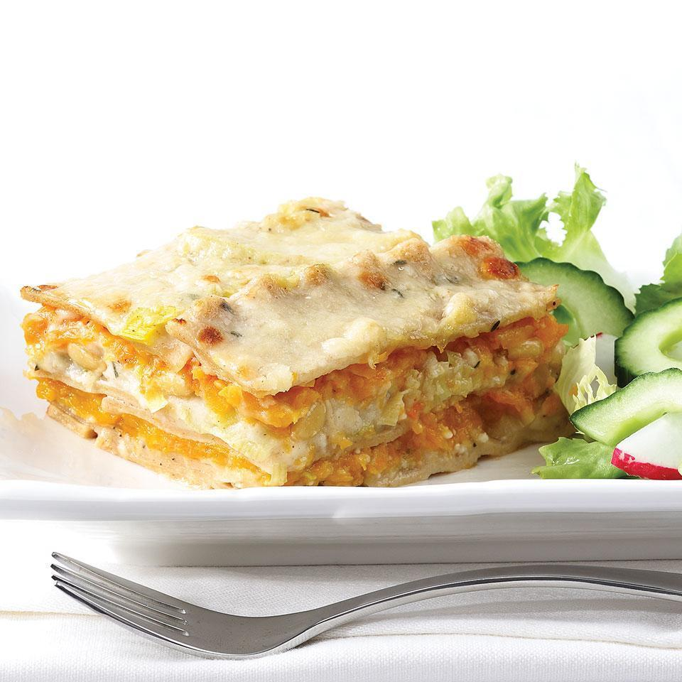 <p>Grated butternut squash, pine nuts and sautéed leeks in a creamy white sauce are layered with sheets of whole-wheat pasta for this wintery variation on a vegetable lasagna. Any Parmesan cheese can be used in this casserole, but we recommend Parmigiano-Reggiano for its superior flavor.</p>