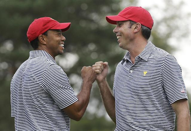 United States team player Tiger Woods, left, and team player Matt Kuchar fist bump after Kuchar made a birdie putt on the fourth hole during a foursome match at the Presidents Cup golf tournament at Muirfield Village Golf Club, Friday, Oct. 4, 2013, in Dublin, Ohio. (AP Photo/Darron Cummings)