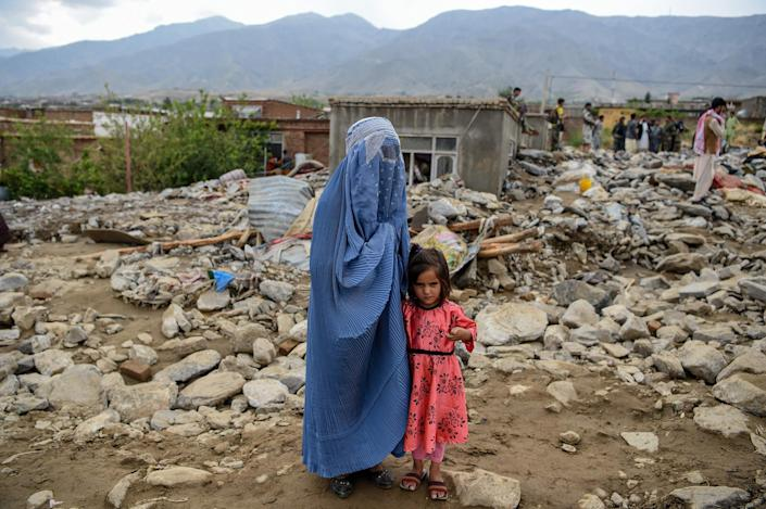 Image: A burqa-clad woman stands near a young girl among households' debris after a flash flood affected the area at Sayrah-e-Hopiyan in Charikar, Afghanistan (Wakil Kohsar / AFP - Getty Images)