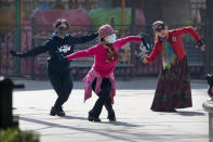 Women wearing face masks to protect against the spread of the coronavirus dance at a public park in Beijing, Friday, Feb. 19, 2021. China has been regularly reporting no locally transmitted cases of COVID-19 as it works to maintain control of the pandemic within its borders. (AP Photo/Mark Schiefelbein)