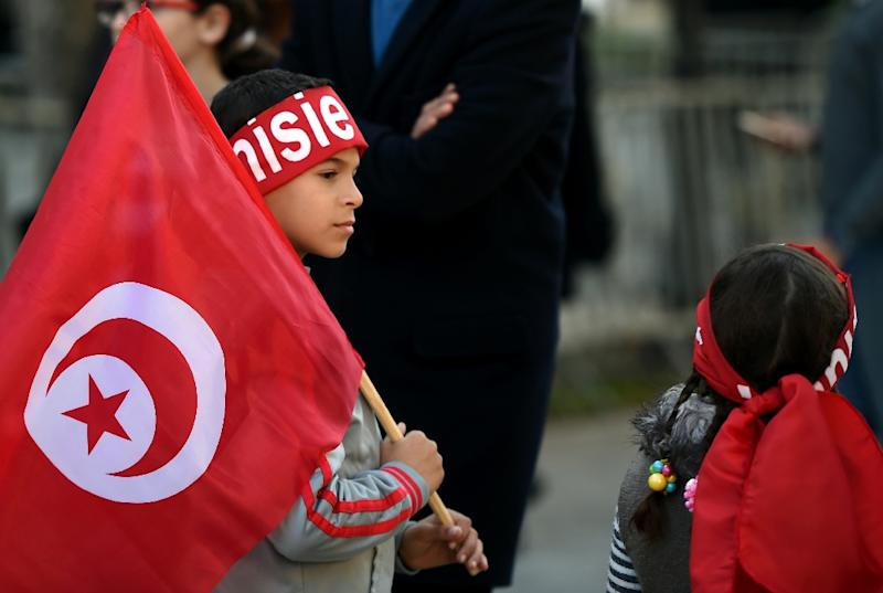 Tunisian children hold national flags at the rally on Habib Bourguiba Avenue (AFP Photo/Fethi Belaid)