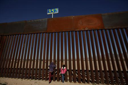 FILE PHOTO: Children peek through the border fence at Anapra neighbourhood in Ciudad Juarez