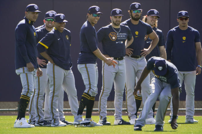 Members of the Milwaukee Brewers watch as Lorenzo Cain, bottom right, fields the ball during the team's spring training baseball workout in Phoenix, Tuesday, Feb. 23, 2021. (AP Photo/Jae C. Hong)