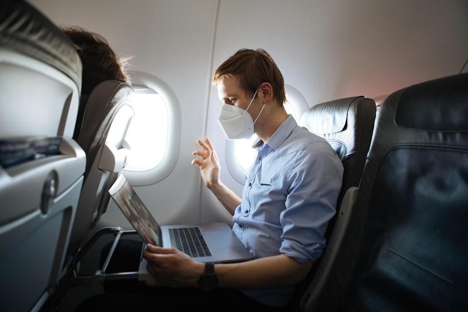 A man wearing face mask while sitting into an airplane. New normal traveling during a pandemic. Male passenger traveling. Wearing FFP2 mask in aircraft cabin. Travel Covid-19 Work from plane on laptop - Credit: Girts - stock.adobe.com