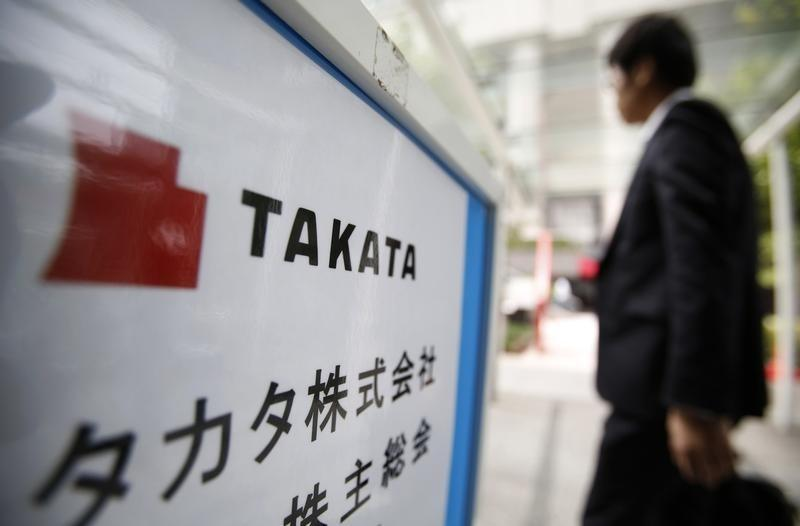 A man walks past a sign board of Japanese auto parts maker Takata Corp's Annual General Meeting in Tokyo
