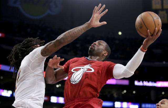 Miami Heat guard Dwyane Wade shoots over Los Angeles Lakers center Jordan Hill during the second half of an NBA basketball game in Los Angeles, Wednesday, Dec. 25, 2013. The Heat won 101-95. (AP Photo/Chris Carlson)