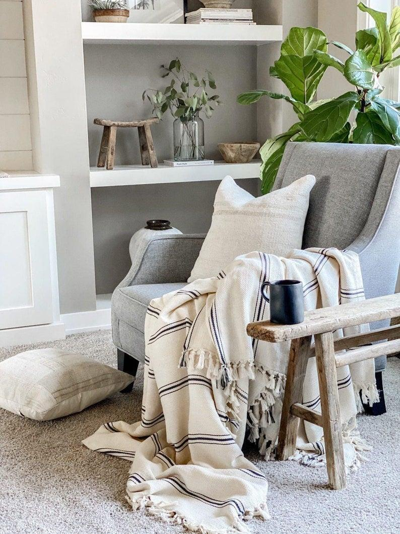 """<h2>Throw Blankets<br></h2><br><h3><h3>FINEGRID Large Turkish Blanket</h3></h3><br>A simple throw blanket makes your couch feel that much comfier <em>and</em> look that much more sophisticated.<br><br><em>Shop <a href=""""https://www.etsy.com/shop/FINEGRID?ref=simple-shop-header-name&listing_id=754101835"""" rel=""""nofollow noopener"""" target=""""_blank"""" data-ylk=""""slk:FINEGRID"""" class=""""link rapid-noclick-resp""""><strong>FINEGRID</strong></a></em><br><br><strong>FINEGRID</strong> Large Turkish Blanket, $, available at <a href=""""https://go.skimresources.com/?id=30283X879131&url=https%3A%2F%2Fwww.etsy.com%2Flisting%2F754101835%2Flarge-turkish-blanket-black-striped%3F"""" rel=""""nofollow noopener"""" target=""""_blank"""" data-ylk=""""slk:Etsy"""" class=""""link rapid-noclick-resp"""">Etsy</a>"""