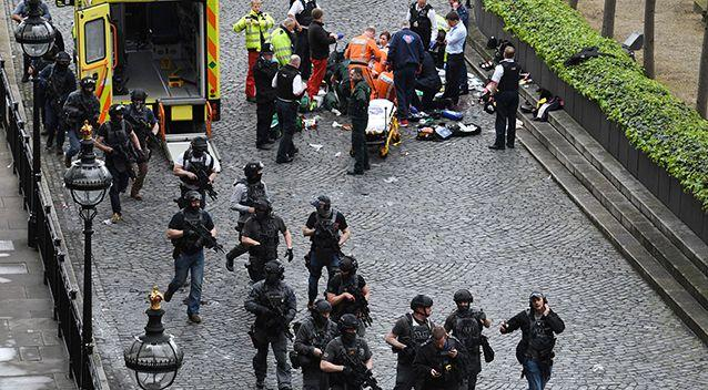 Armed police swarm the scene near Westminster as the injured are treated. Photo: AP