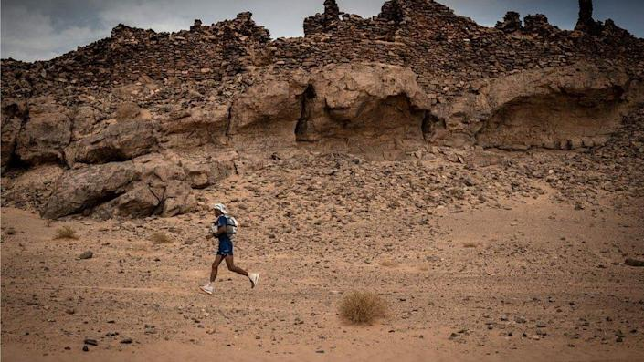 A man running in the Sahara. Most of the photo shows the arid desert in the background with a rocky landscape and it is sandy all over.