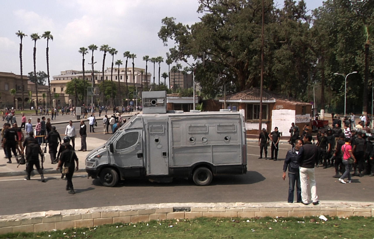 In this image taken from AP Television, Egyptian security forces inspect the scene after multiple explosions hit the area outside the main campus of Cairo University, killing at least two, in Giza, Egypt, Wednesday, April 2, 2014. The bombings targeted riot police routinely deployed at the location in anticipation of near-daily protests by students who support ousted Islamist President Mohammed Morsi and his Muslim Brotherhood group. (AP Photo/AP Video)