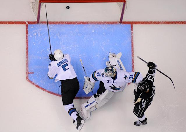 Los Angeles Kings center Jeff Carter, right, scores on San Jose Sharks goalie Antti Niemi, center, of Finland, as defenseman Jason Demers dives in an attempt to stop it during the third period in Game 3 of an NHL hockey first-round playoff series, Tuesday, April 22, 2014, in Los Angeles. (AP Photo/Mark J. Terrill)
