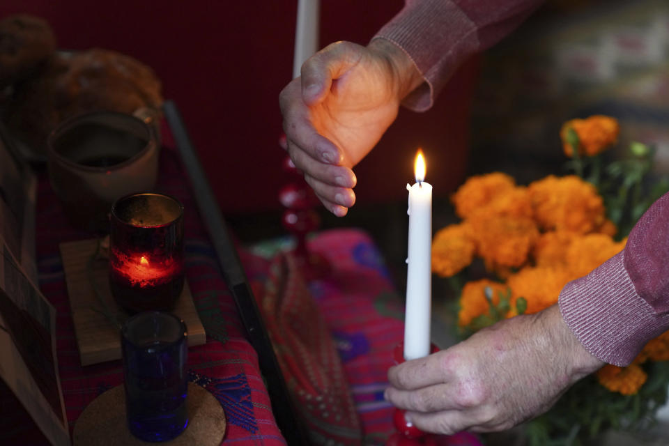 "Sebastian Diaz Aguirre steadies a candle in an altar dedicated to his father, who died in a nursing home in Mexico last month, for Day of the Dead in his home in the Brooklyn borough of New York, Wednesday, Oct. 28, 2020. ""He didn't die of COVID, but me and my brother said the same exact thing, that it was the pandemic that killed him,"" said Diaz Aguirre. (AP Photo/Emily Leshner)"