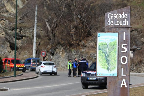 Policemen patrol on a road near Isola Village (French Alps) where a mountain cottage has been destroyed by a rockslide which killed two children aged seven and ten, on February 23, 2014.  Both children and their families from the region, arrived yesterday in the village where they occupied an old barn located on a cliff. AFP PHOTO / JEAN CHRISTOPHE MAGNENET        (Photo credit should read JEAN CHRISTOPHE MAGNENET/AFP/Getty Images)