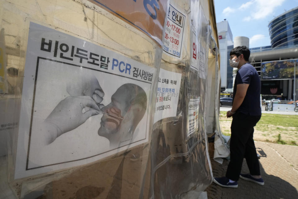 """A man waits to get coronavirus testing at a makeshift testing site in Seoul, South Korea, Friday, July 16, 2021. South Korean officials are pushing for tightened pandemic restrictions beyond the hard-hit capital area as they wrestle with a record-breaking surge in coronavirus cases. The signs on a banner at left read """"How to check Polymerase Chain Reaction."""" (AP Photo/Ahn Young-joon)"""