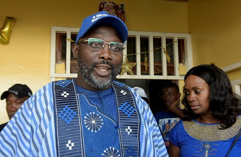 Presidential candidate and former football star George Weah, flanked by his wife Clar in Monrovia on December 23, 2017. Weah is tipped to become president on Tuesday
