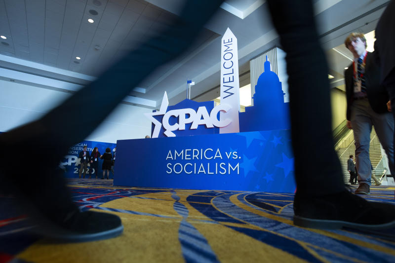 People pass by the CPAC sign, during Conservative Political Action Conference, CPAC 2020, at the National Harbor, in Oxon Hill, Md., Friday, Feb. 28, 2020. (AP Photo/Jose Luis Magana)