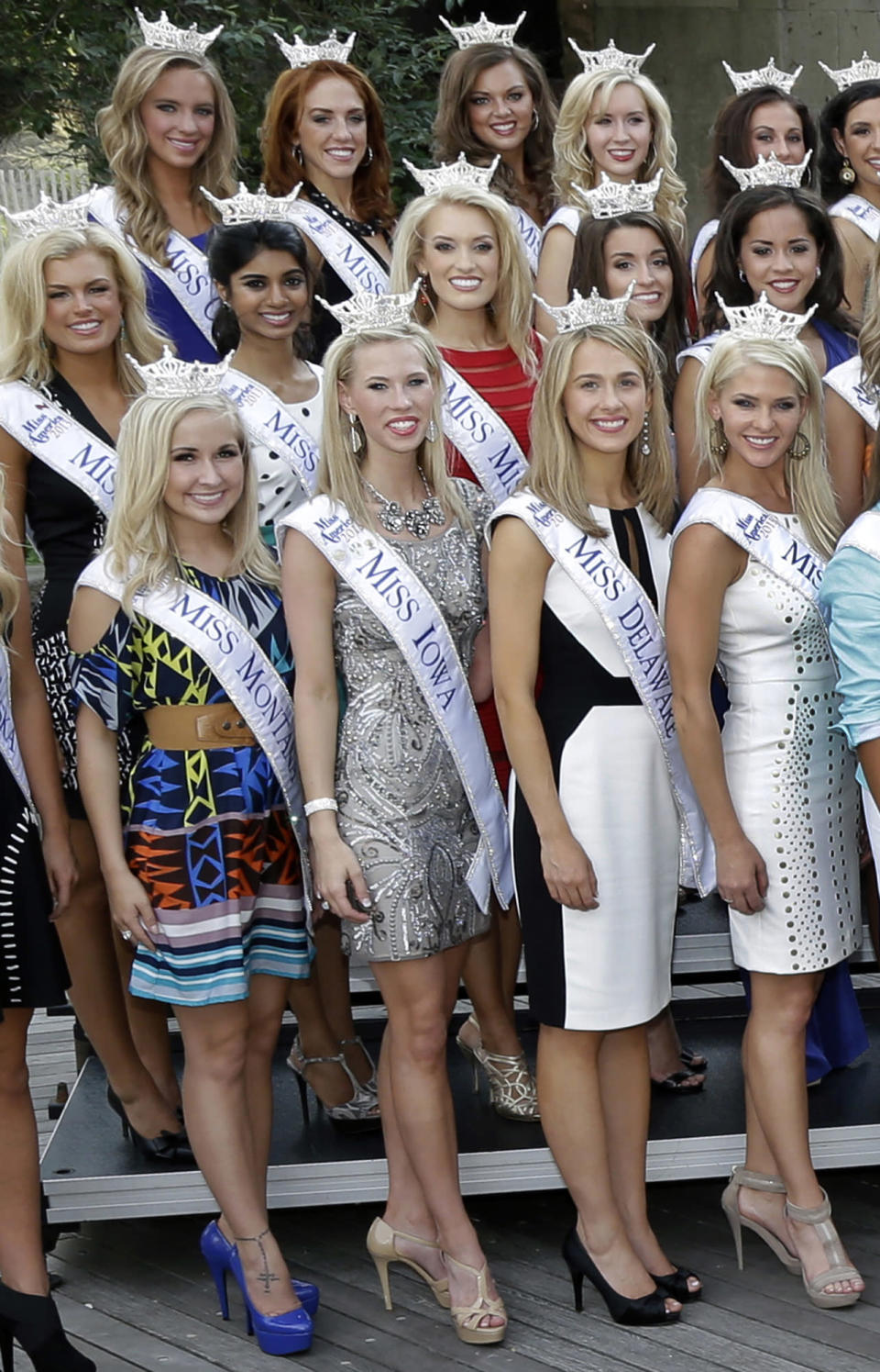 In this Tuesday, Sept. 3, 2013, photograph, Miss Iowa, Nicole Kelly, front row, second from left, stands with other Miss America contestants during arrival ceremonies in Atlantic City, N.J. Kelly was born without part of her left forearm and says she has never let her disability get in the way of doing what she wanted. (AP Photo/Mel Evans)