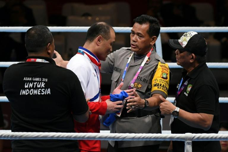 North Korean boxing coach Pak Chol Jun is restrained by a policeman and security officials after boxer Pang Chol Mi lost a final on Saturday. He was thrown out of the Asian Games
