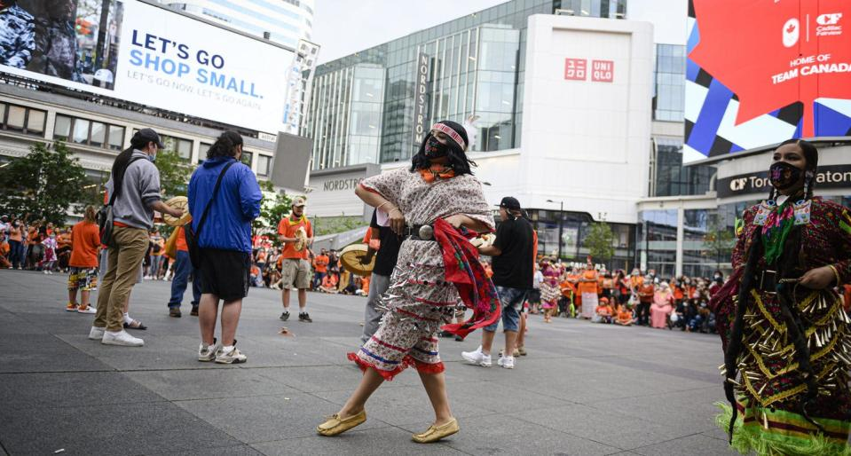 Two jingle dancers dance at a public square under advertisemennts and an ad for Team Canada.