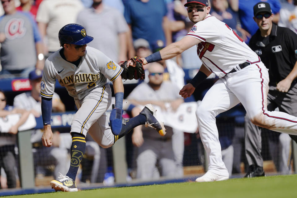 Milwaukee Brewers third baseman Luis Urias (2) is tagged out by Atlanta Braves third baseman Austin Riley (27) after he was caught in a rundown during the fifth inning of Game 3 of a baseball National League Division Series, Monday, Oct. 11, 2021, in Atlanta. (AP Photo/John Bazemore)