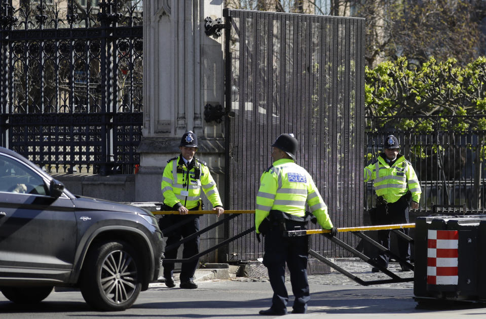 Police officers check a car driving through an entrance to parliament as the country is in lockdown to help curb the spread of coronavirus, in London, Tuesday, April 21, 2020. Britain's Parliament is going back to work, and the political authorities have a message for lawmakers: Stay away. U.K. legislators and most parliamentary staff were sent home in late March as part of a nationwide lockdown to slow the spread of the new coronavirus. With more than 16,500 people dead and criticism growing of the government's response to the pandemic, legislators are returning Tuesday — at least virtually — to grapple with the crisis. (AP Photo/Kirsty Wigglesworth)