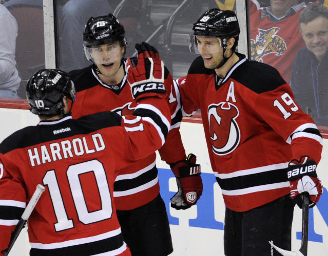 New Jersey Devils' Travis Zajac, right, celebrates his goal with Peter Harrold (10) and Tuomo Ruutu, of Finland, during the third period of an NHL hockey game against the Florida Panthers Monday, March 31, 2014, in Newark, N.J. The goal was Zajac's third goal for a hat trick as the Devils won 6-3. (AP Photo/Bill Kostroun)