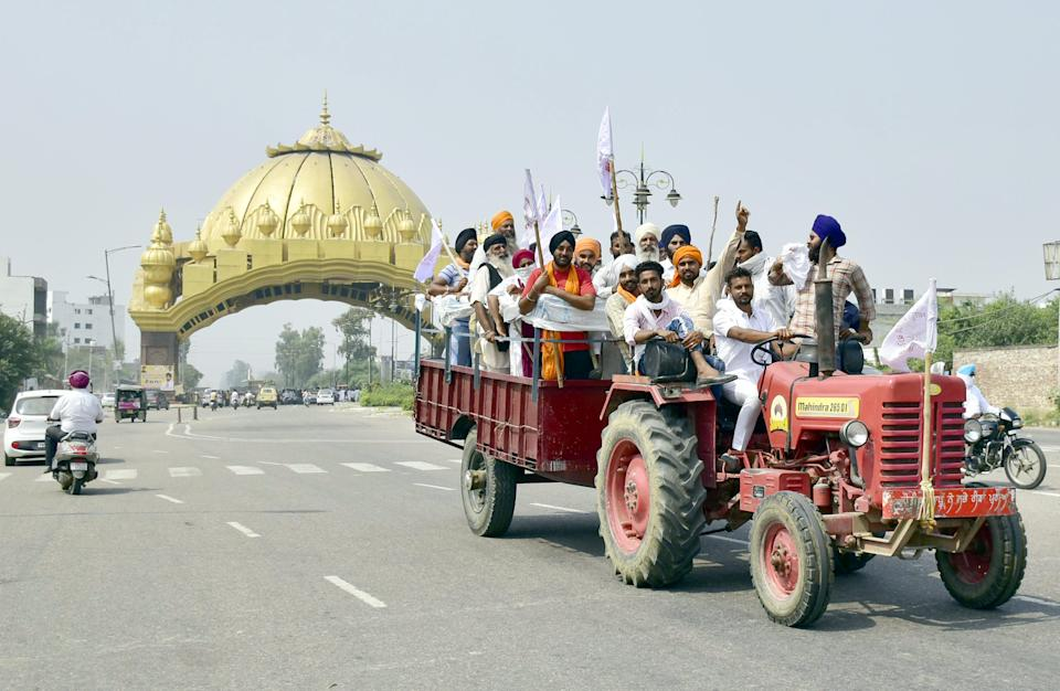 AMRITSAR, INDIA SEPTEMBER 25: Farmers onboard a tractor shout slogans during Punjab Bandh, a statewide farmers' strike, against the passing of agriculture bills in the Parliament, at Golden gate, on September 25, 2020 in Amritsar, India. The two bills - the Farmers (Empowerment and Protection) Agreement on Price Assurance and Farm Services Bill, 2020 and the Farming Produce Trade and Commerce (Promotion and Facilitation) Bill, 2020 - were passed by the Rajya Sabha despite uproar and strong protest by the Opposition parties in the house. (Photo by Sameer Sehgal/Hindustan Times via Getty Images)