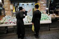 Ultra-Orthodox Jewish men speak to a vendor at a fruit and vegetable stall in a market in Jerusalem May 11, 2017. Picture taken May 11, 2017. REUTERS/Amir Cohen