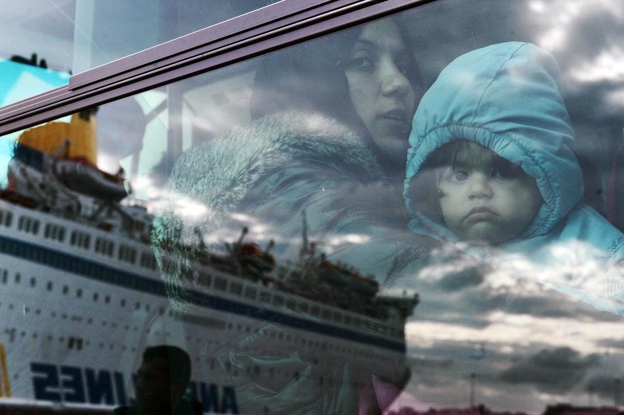 A woman and a child peer from a bus, after migrants and refugees disembarked from a government chartered ferry, seen in reflection, in the port of Piraeus in Athens on November 27, 2015.