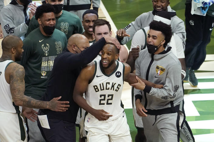 Milwaukee Bucks forward Khris Middleton (22) celebrates with teammates during the second half against the Phoenix Suns in Game 4 of basketball's NBA Finals in Milwaukee, Wednesday, July 14, 2021. (AP Photo/Paul Sancya)