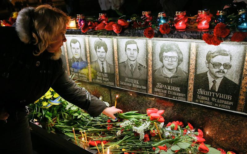Ukrainians light candles and lay flowers at the memorial for 'liquidators' who died during cleaning up works after the Chernobyl nuclear power plant disaster, during a ceremony in Slavutich city, some 190 km north of the capital Kiev, Ukraine, early 26 April 2016. - Credit: SERGEY DOLZHENKO