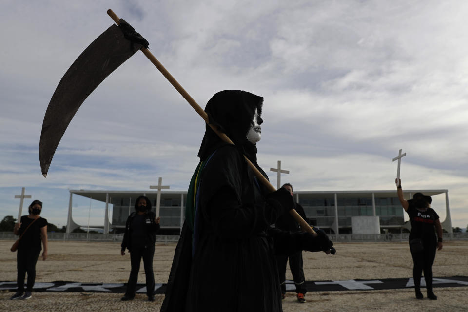 A demonstrator dressed as death performs outside Planalto presidential palace to protest the president's handling of the COVID-19 pandemic in Brasilia, Brazil, Friday, March 26, 2021. Brazil surpassed 300,000 deaths from the virus this week. (AP Photo/Eraldo Peres)