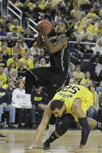 Purdue guard Terone Johnson, top, shoots over Michigan forward Jordan Morgan (52) during the second half of an NCAA college basketball game at Crisler Center in Ann Arbor, Mich., Saturday, Feb. 25, 2012. Johnson finished with 22 points in Purdue's 75-61 win. (AP Photo/Carlos Osorio)