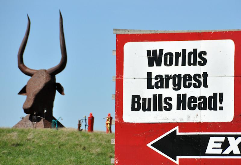 "In this May 10, 2012 photo, an Interstate 90 billboard billing a bull's head sculpture as the world's largest sits at the edge of Porter Sculpture Park, in Montrose, S.D. The park's signature piece is a 60-foot-tall Egyptian-style bull's head that stares down Interstate 90 motorists as they head out to South Dakota's Black Hills. Wayne Porter spent three years creating the 25-ton monstrosity out of railroad tie plates, dubbing it ""The World's Largest Bull's Head"" on a nearby billboard. (AP Photo/Dirk Lammers)"