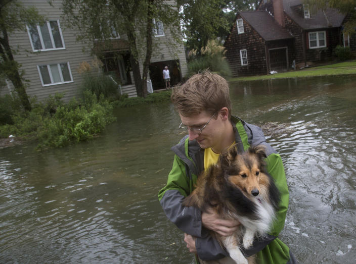 Fred Lenihan carries Ollie, a six-year-old Sheltie, through floodwaters in Larchmont after Hurricane Dorian brought heavy wind and rain to Norfolk, Va., on Friday, Sept. 6, 2019. (Kaitlin McKeown/The Virginian-Pilot via AP)