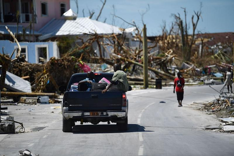 Residents pass damage caused by Hurricane Dorian on Sept. 5, 2019, in Marsh Harbour, Great Abaco Island in the Bahamas. | Brendan Smialowski—AFP/Getty Images