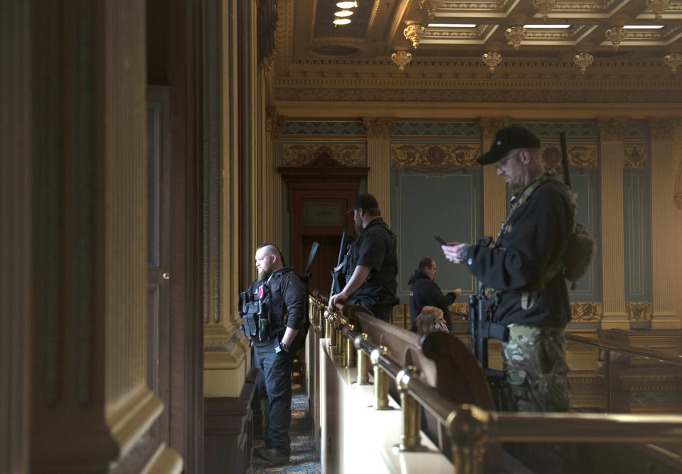 FILE - In this April 30, 2020, file photo, armed members of a militia group watch the protest outside while waiting for the Michigan Senate to vote at the Capitol in Lansing, Mich. In the past year, insurrectionists have breached the U.S. Capitol and protesters have forced their way into statehouses around the country. But the question of whether guns should be allowed in capitol buildings remains political and states are going in opposite directions. (Nicole Hester/MLive.com/Ann Arbor News via AP File