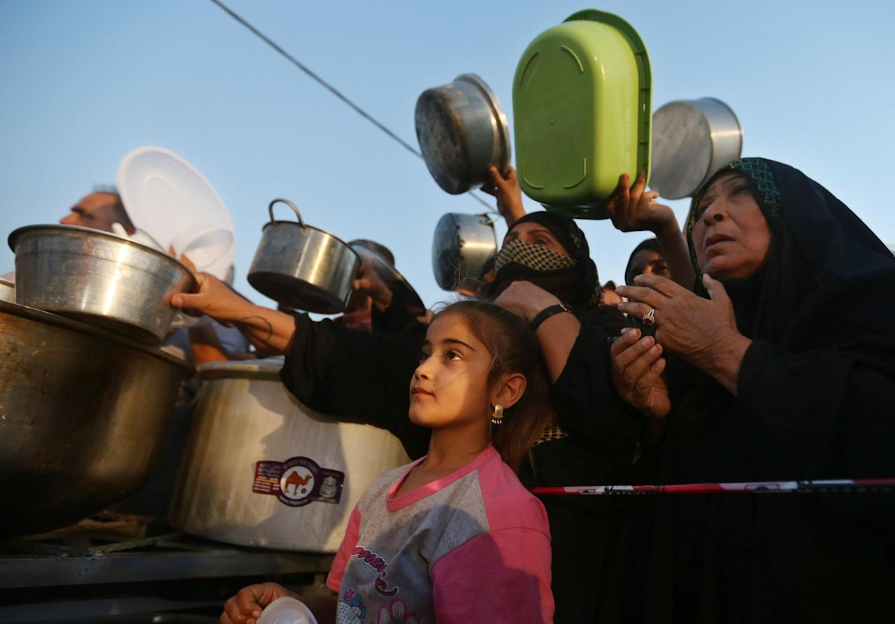 In this Sunday, June 29, 2014 photo, displaced Iraqi women hold pots as they queue to receive food during the first day of the Islamic holy month of Ramadan, at an encampment for displaced Iraqis who fled from Mosul and other towns, in the Khazer area outside Irbil, north Iraq. The chaotic scene underscored the fearful insecurity of displaced Iraqis as they begin Ramadan in a nation threatened by conflict and political rivalries among Shiites, Sunnis and Kurds. (AP Photo/Hussein Malla)