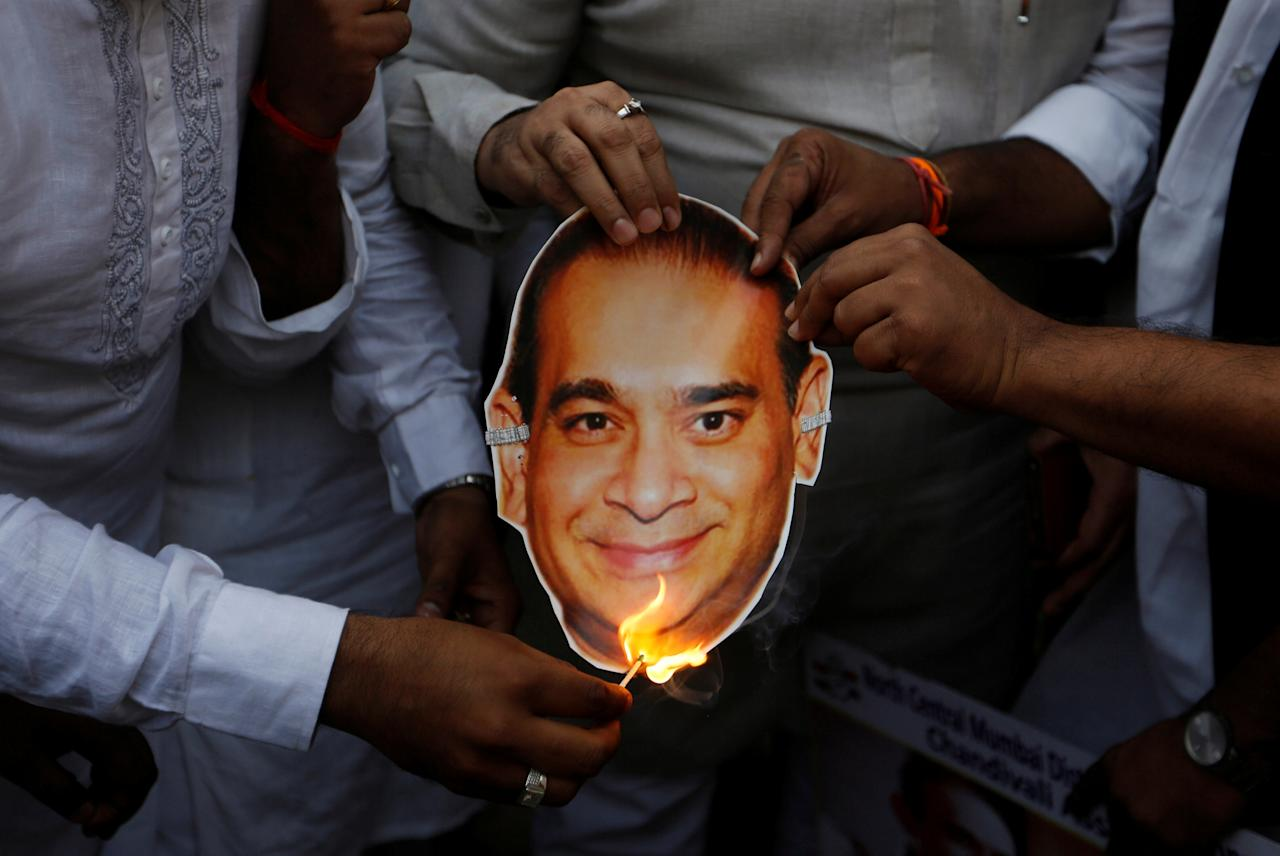 Activists of the youth wing of India's main opposition Congress party burn a cut-out with an image of billionaire jeweller Nirav Modi during a protest in Mumbai, India, February 23, 2018. REUTERS/Francis Mascarenhas