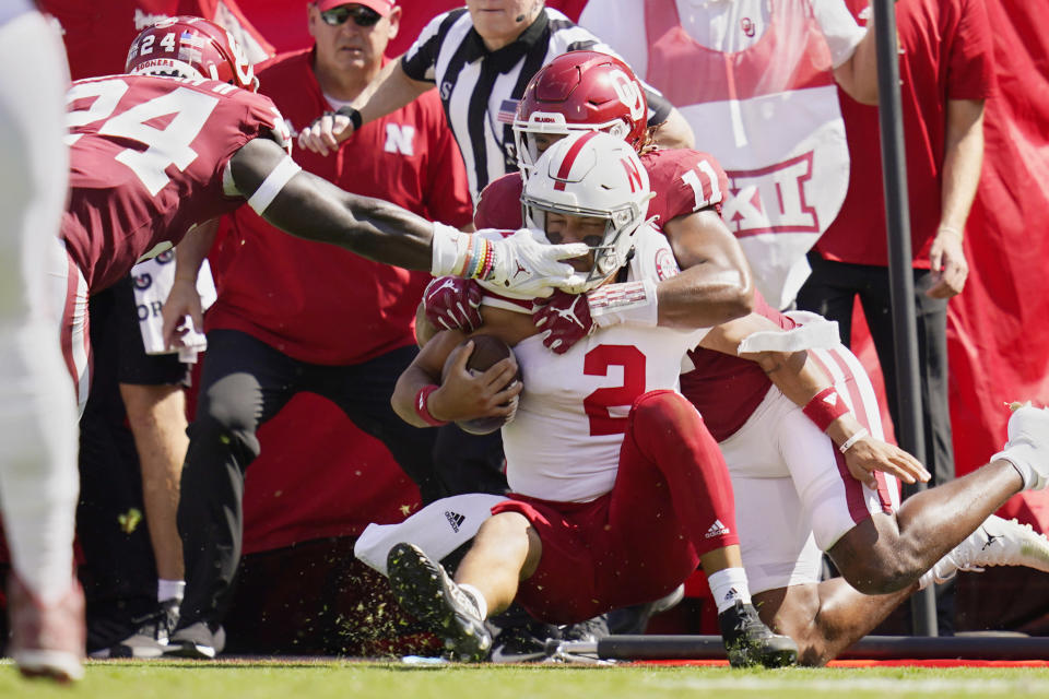 Nebraska quarterback Adrian Martinez (2) is brought down by Oklahoma linebackers Nik Bonitto (11) and Brian Asamoah (24) in the first half of an NCAA college football game, Saturday, Sept. 18, 2021, in Norman, Okla. (AP Photo/Sue Ogrocki)
